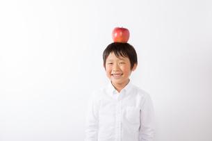 りんごを頭にのせる少年の写真素材 [FYI01163916]