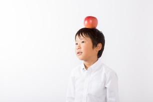 りんごを頭にのせる少年の写真素材 [FYI01163918]