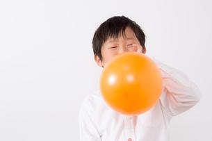 風船を膨らます少年の写真素材 [FYI01163998]