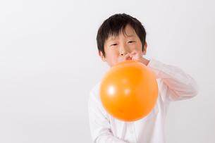風船を膨らます少年の写真素材 [FYI01163999]