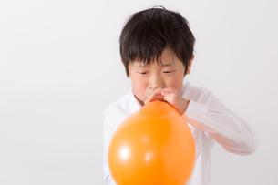 風船を膨らます少年の写真素材 [FYI01164000]