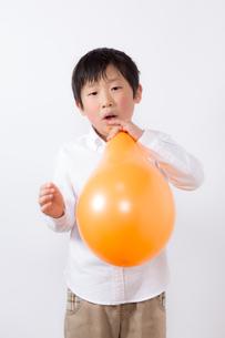 風船を膨らます少年の写真素材 [FYI01164001]