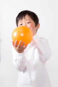 風船を膨らます少年の写真素材 [FYI01164002]