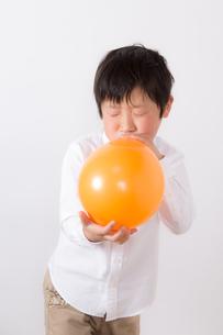 風船を膨らます少年の写真素材 [FYI01164003]