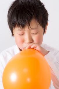 風船を膨らます少年の写真素材 [FYI01164004]