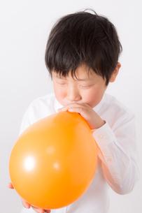 風船を膨らます少年の写真素材 [FYI01164005]
