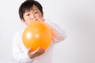 風船を膨らます少年の写真素材 [FYI01164006]