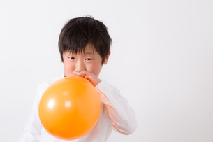 風船を膨らます少年の写真素材 [FYI01164007]
