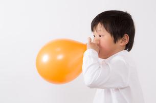 風船を膨らます少年の写真素材 [FYI01164008]