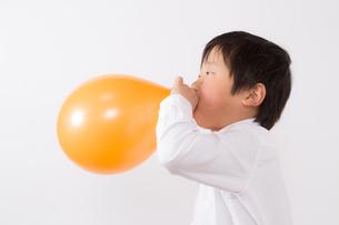 風船を膨らます少年の写真素材 [FYI01164009]