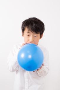 風船を膨らます少年の写真素材 [FYI01164025]
