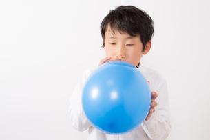 風船を膨らます少年の写真素材 [FYI01164026]
