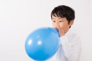 風船を膨らます少年の写真素材 [FYI01164033]