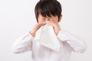 鼻をかむ少年の写真素材 [FYI01164047]