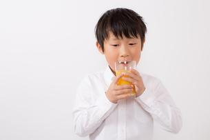 オレンジジュースを飲む少年の写真素材 [FYI01164050]