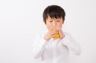 オレンジジュースを飲む少年の写真素材 [FYI01164051]