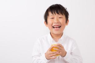 オレンジジュースを持つ笑顔の少年の写真素材 [FYI01164052]