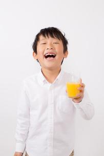 オレンジジュースを持つ笑顔の少年の写真素材 [FYI01164054]