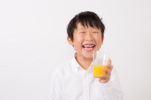 オレンジジュースを持つ笑顔の少年の写真素材 [FYI01164055]