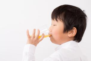 オレンジジュースを飲む少年の写真素材 [FYI01164057]