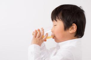 オレンジジュースを飲む少年の写真素材 [FYI01164058]