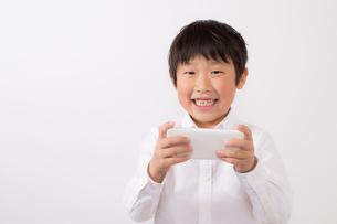 スマーフォンで遊ぶ少年の写真素材 [FYI01164059]