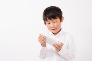 スマーフォンで遊ぶ少年の写真素材 [FYI01164063]