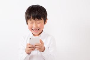 スマーフォンで遊ぶ少年の写真素材 [FYI01164064]