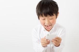 スマーフォンで遊ぶ少年の写真素材 [FYI01164067]