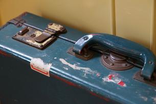 部屋の壁際に置かれた古い汚れたトランクの写真素材 [FYI01166188]