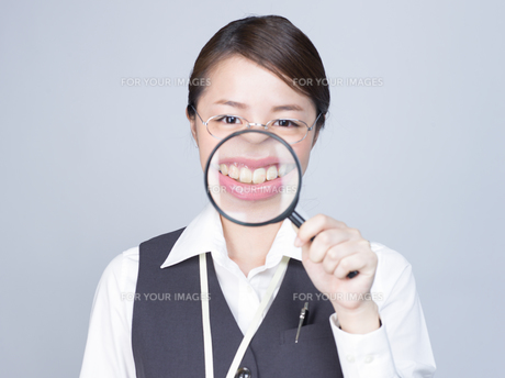 大きな虫眼鏡で口元を拡大する女性の写真素材 [FYI01166306]