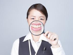 大きな虫眼鏡で口元を拡大する女性の写真素材 [FYI01166307]