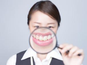 大きな虫眼鏡で口元を拡大する女性の写真素材 [FYI01166310]