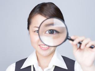 大きな虫眼鏡で見ている女性の写真素材 [FYI01166311]