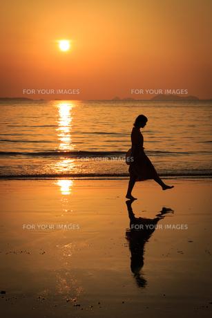 夕日の砂浜を歩く女性の写真素材 [FYI01166926]