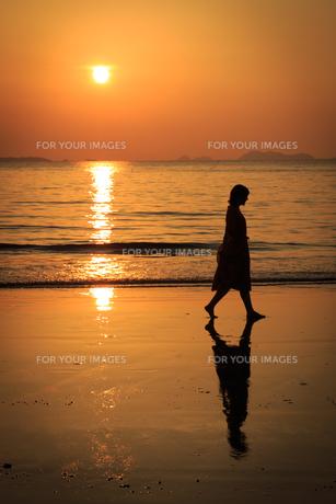 夕日の砂浜を歩く女性の写真素材 [FYI01166927]