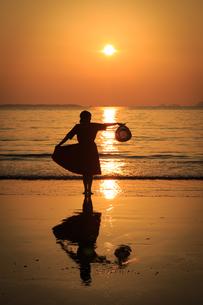 夕日の砂浜を歩く女性の写真素材 [FYI01166928]