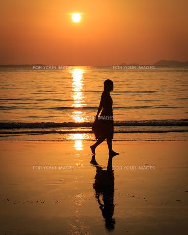 夕日の砂浜を歩く女性の写真素材 [FYI01166929]