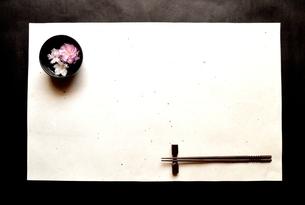 白い和紙の上の黒い小鉢にいけた桜と箸 の写真素材 [FYI01168613]
