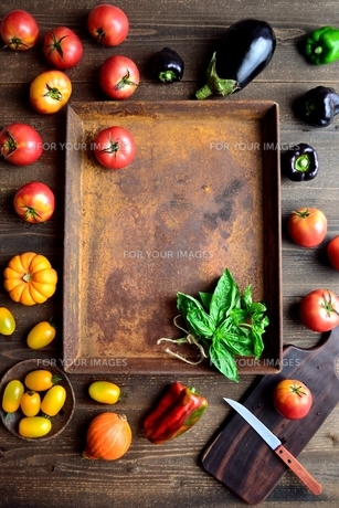 錆びたトレーとトマトとバジルリーフとまな板の写真素材 [FYI01169048]