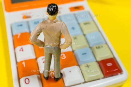 電卓の上に立つ男性の写真素材 [FYI01169477]