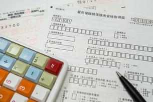 雇用保険の書類と電卓の写真素材 [FYI01169490]