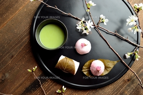 黒いおぼんの上の桜の和菓子と抹茶と桜の写真素材 [FYI01169686]
