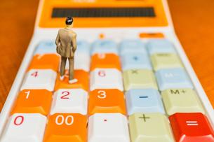 電卓の上に立つ男性の写真素材 [FYI01169751]