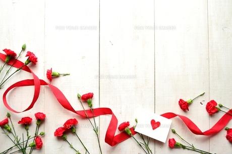 リボンと赤いカーネーションとメッセージカードの写真素材 [FYI01169932]