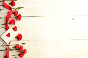 たくさん並べた赤いカーネーションとハートのメッセージカード 白木材背景の写真素材 [FYI01170559]