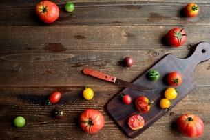 カラフルなトマトとまな板 黒木材背景の写真素材 [FYI01170924]