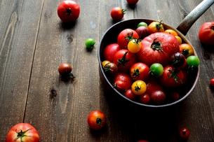 鍋に盛ったカラフルなトマト 黒木材背景の写真素材 [FYI01170928]