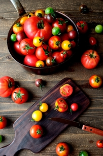 鍋に盛ったカラフルなトマトとまな板 黒木材背景の写真素材 [FYI01170930]