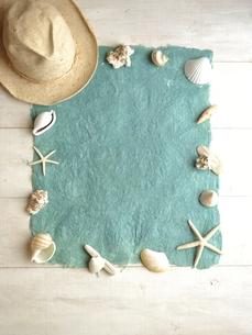 白い貝がらと水色の紙と麦わら帽子の写真素材 [FYI01170934]